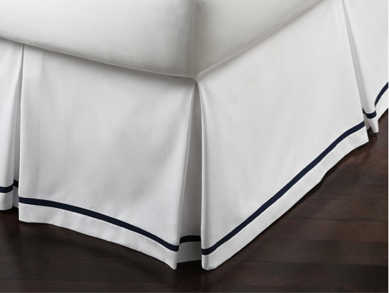 Corner of a white tailored bed skirt with black detailing