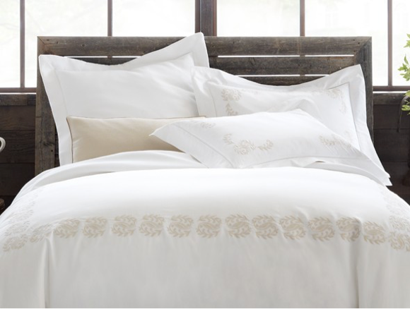 A white bed with embroidered accents in linen