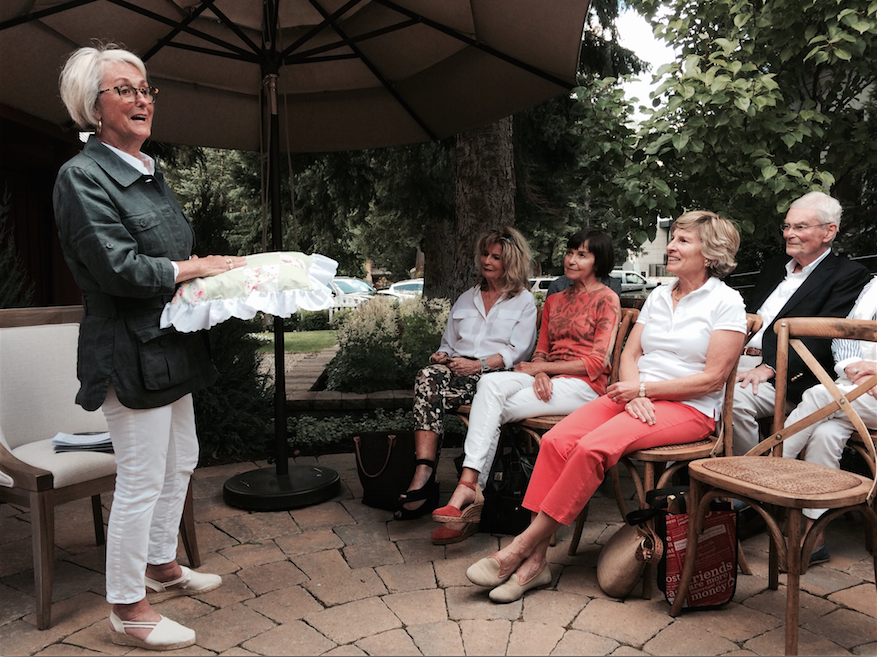Peacock Alley Founder Mary Ella Gabler speaks to an audience on an outdoor patio at The Picket Fence in Ketchum, Idaho