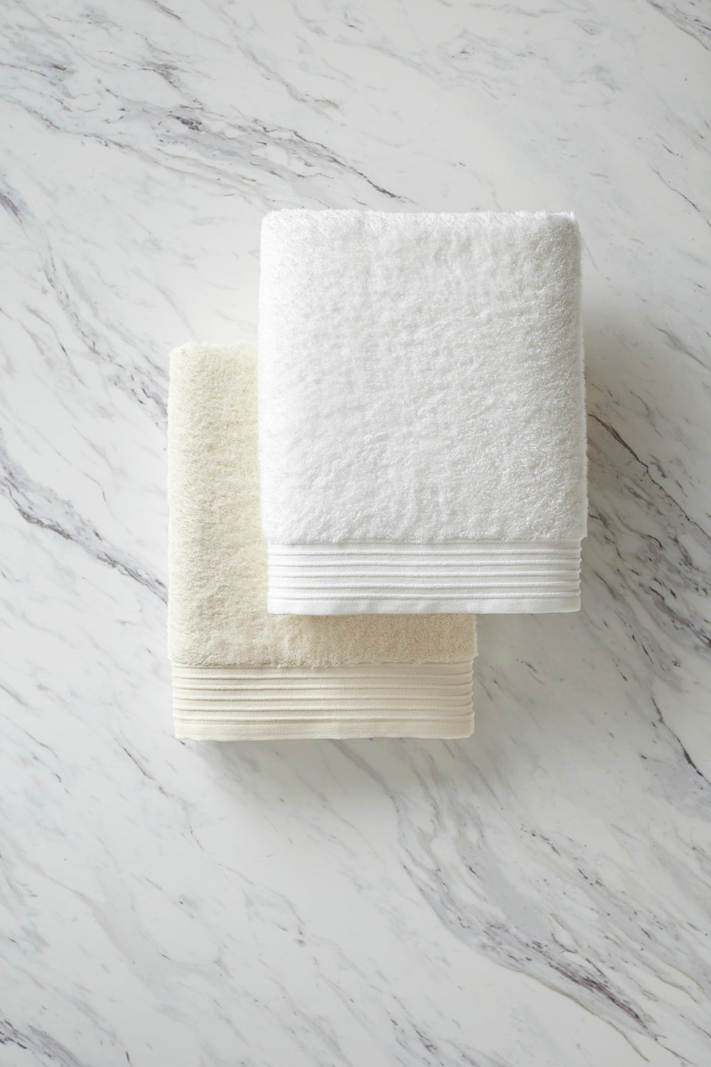Minimalist folded Bamboo towels in white and ivory on a white marble background