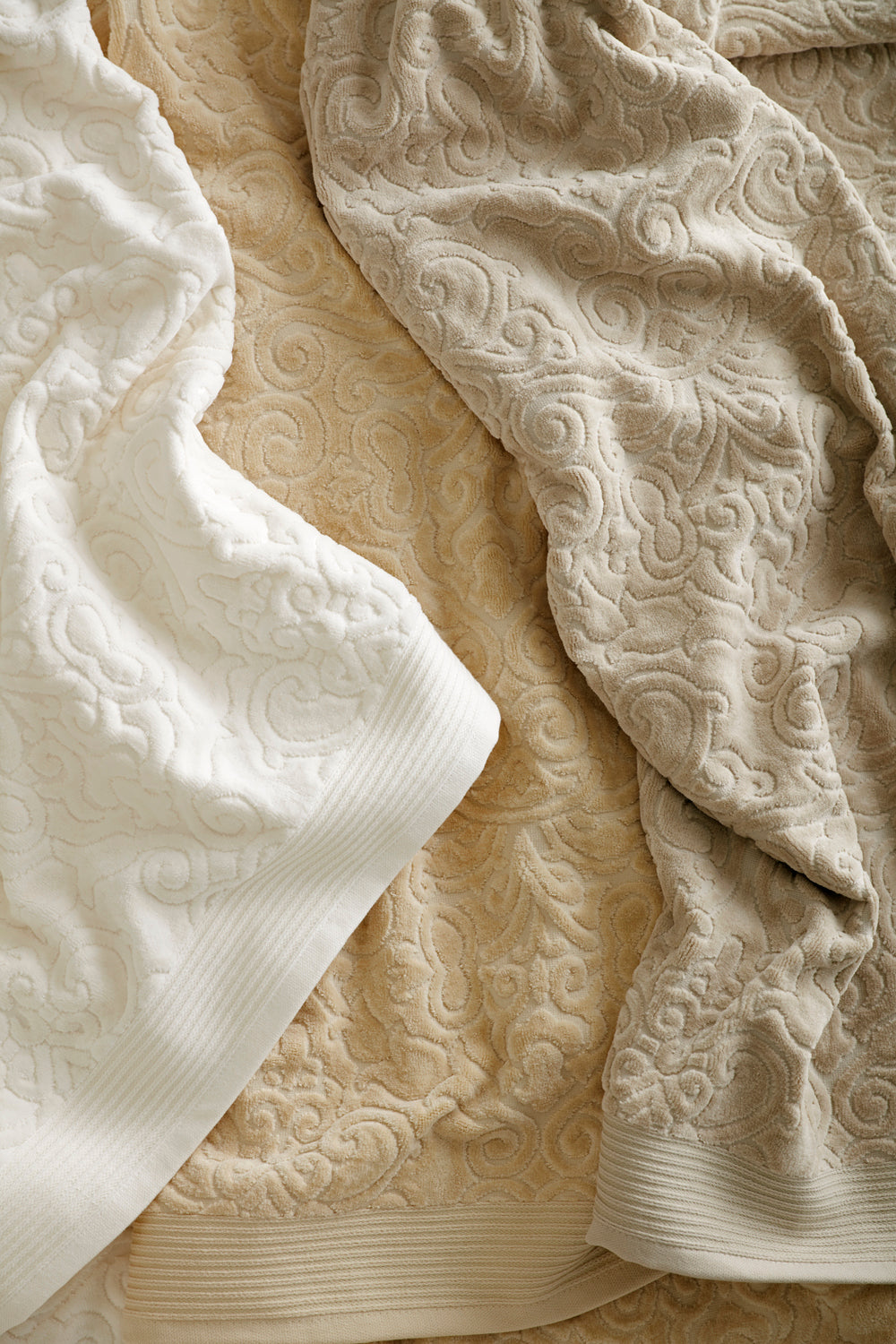Towels in various neutral colors featuring a retro damask pattern in a sculpted velour