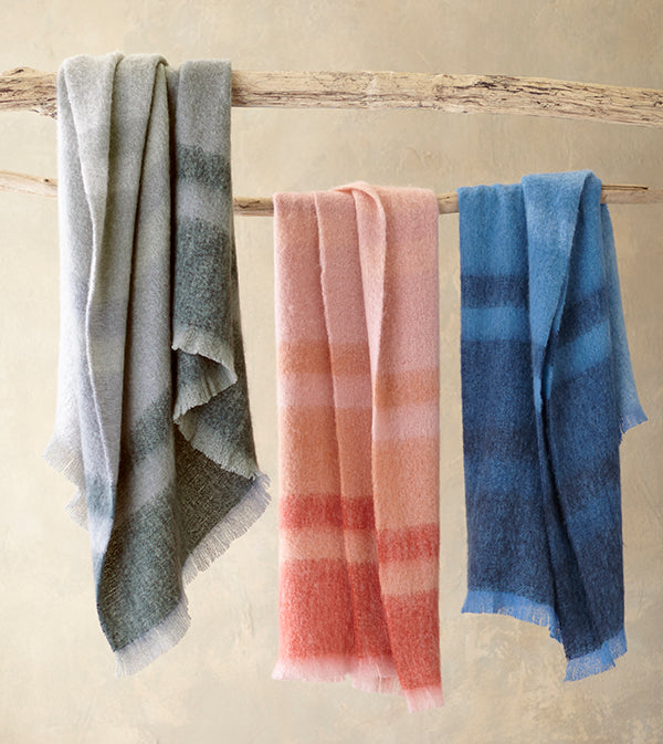 Durban Mohair Throw blankets in gray, spice and navy, draped over a branch
