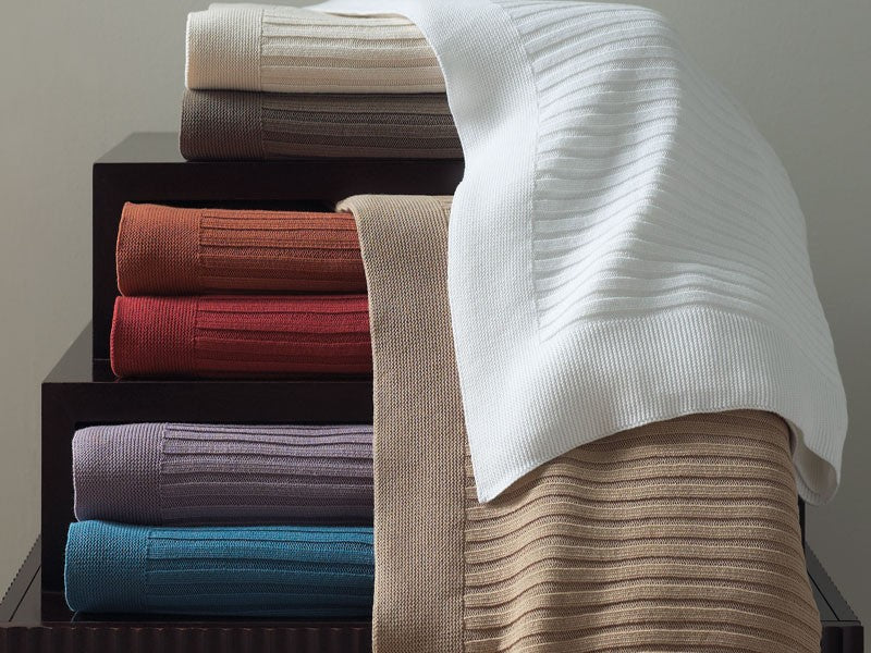 A stack of richly colored knit ribbed throw blankets