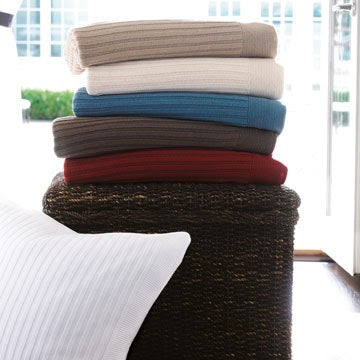 A stack of richly colored knit blankets folded on top of a wicker hamper