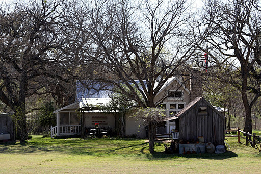 A farmhouse and outbuildings tucked among the trees in Granbury, TX