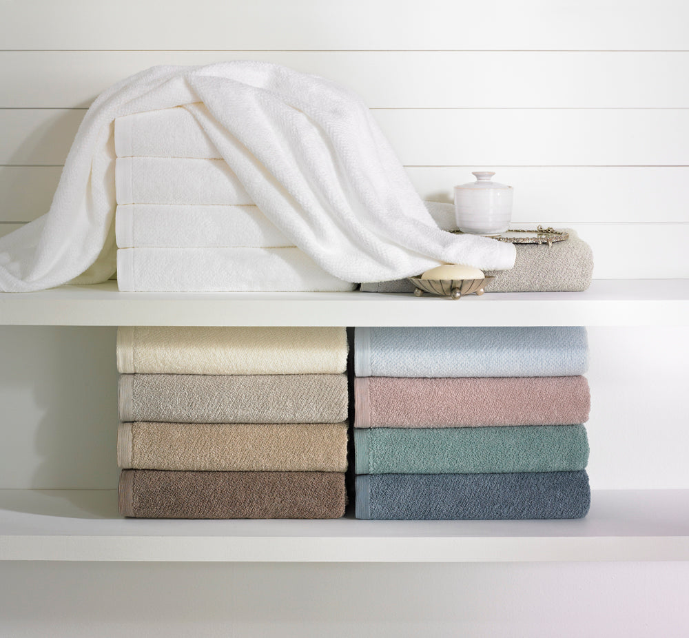 Folded towels in various colors against a white board background