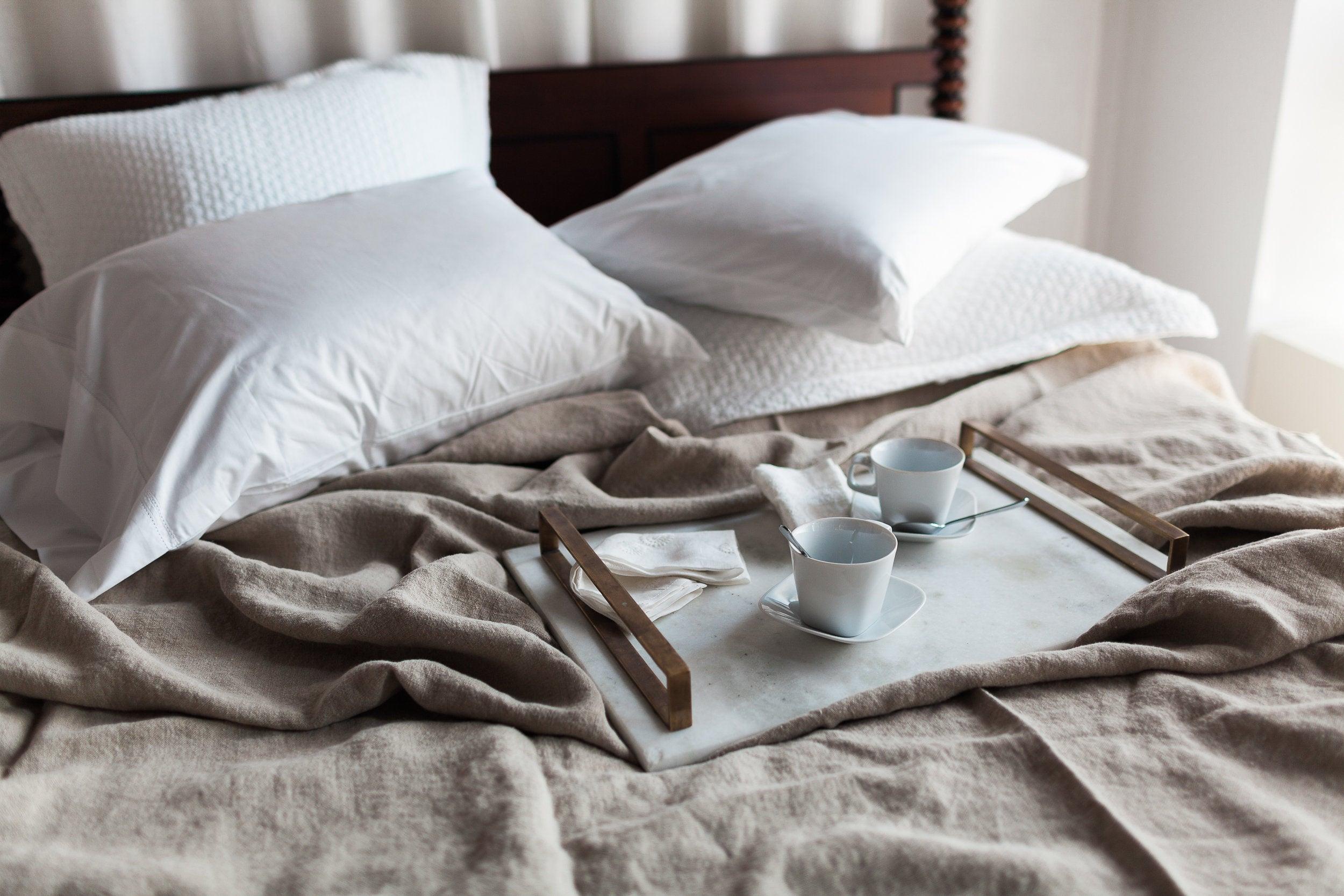 Messy bed featuring various textured linens with a breakfast tray and empty coffee cups