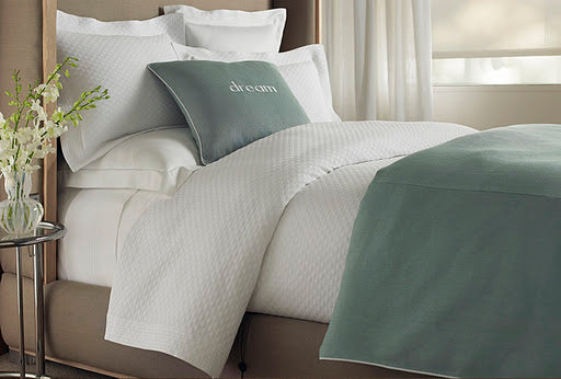 White bed with luxurious textures and green coverlet and throw pillow