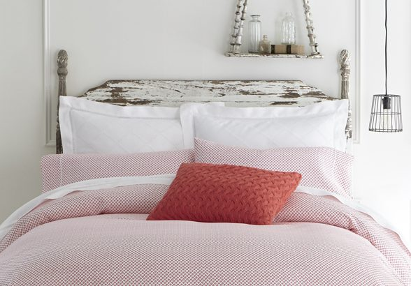 Country style bed made up in red and white with a cable knit throw pillow on top