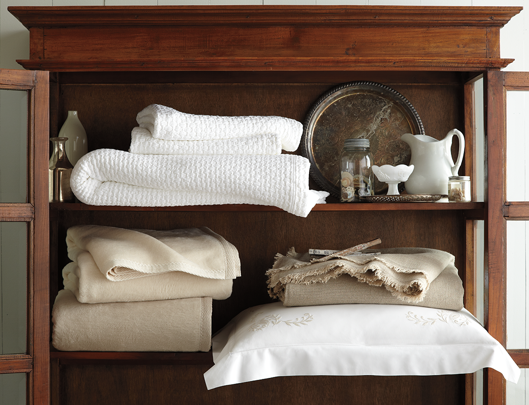 A selection of luxury bedding linens folded and shelved with other household decor items