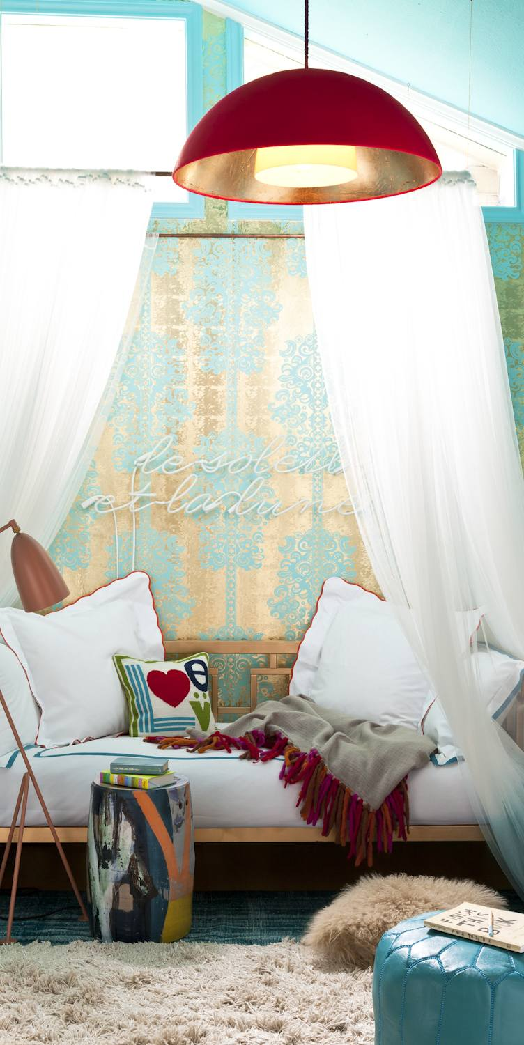 Canopy daybed surrounded in tones of turquoise and copper
