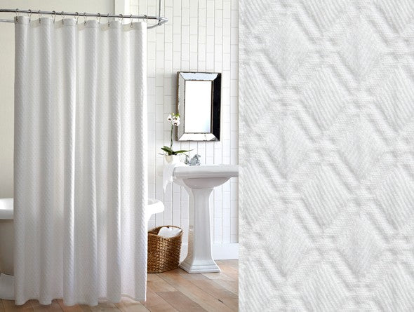 White cotton diamond design matelassé shower curtain in a mostly white bathroom