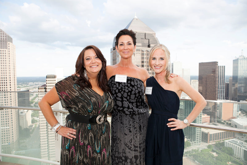 Three lovely ladies pose on the balcony in front of the Dallas skyline