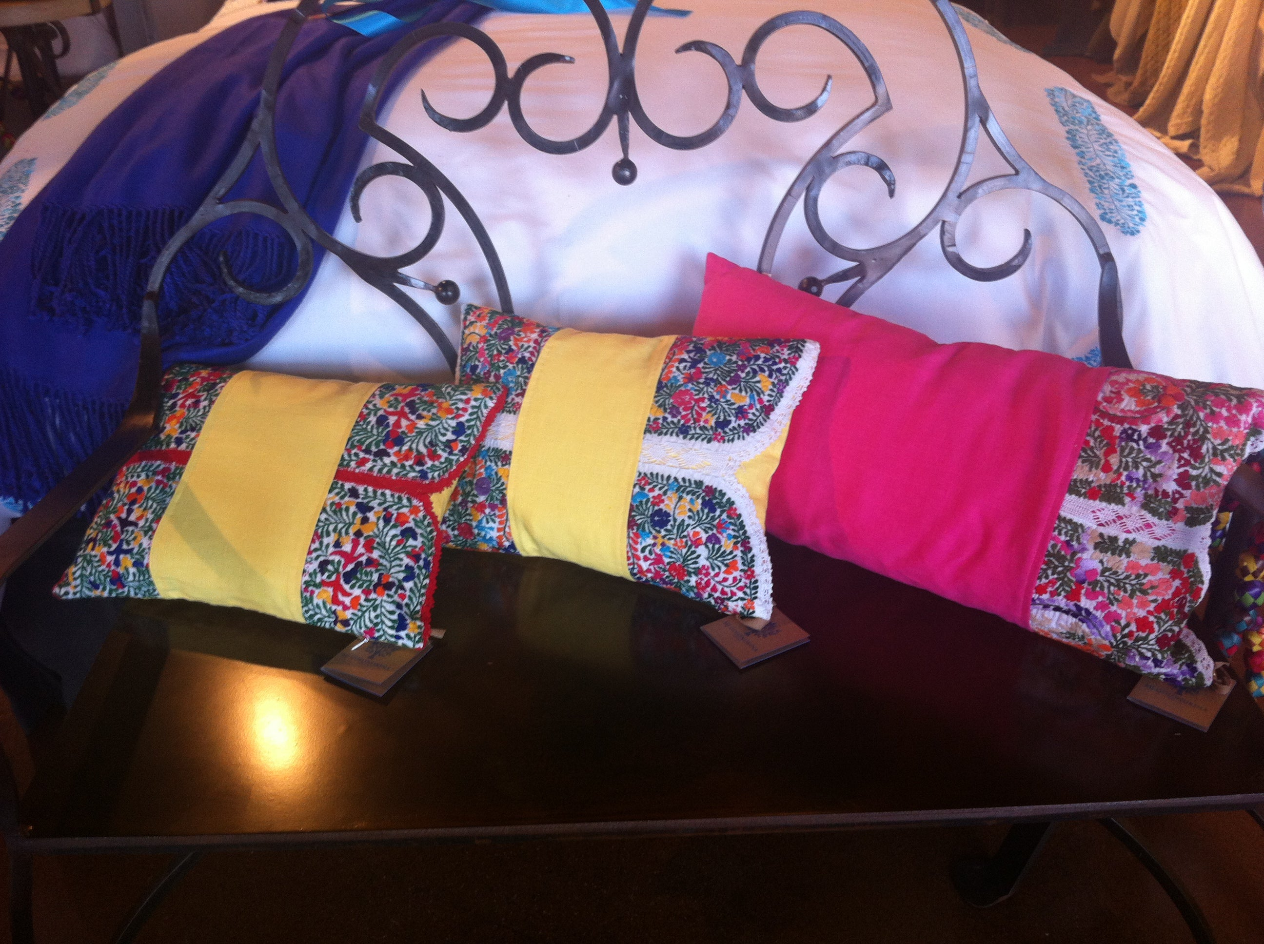 Colorful pillows with Mexican flair displayed on a bench at the foot of a bed