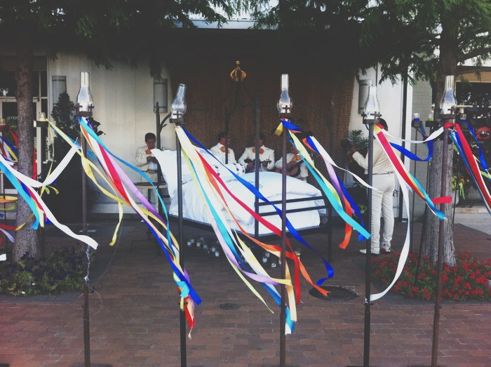 Iron posts decorated with brightly colored ribbon hold candles while a mariachi band plays around an all white bed