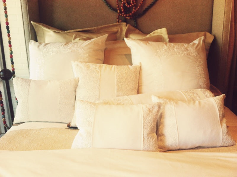 White and neutral bedding with lace and embroidery on the pillows