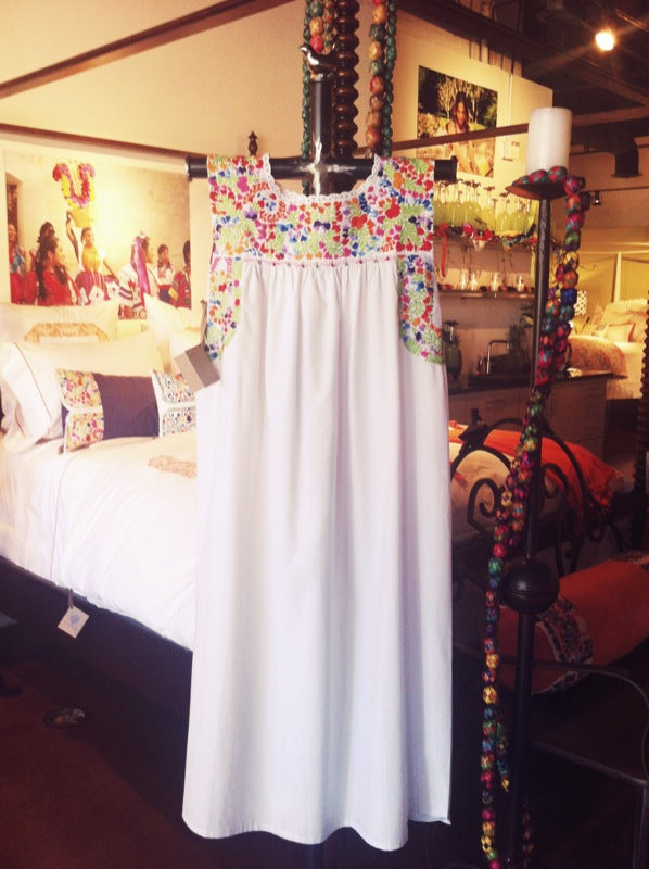 A Mi Golondrina dress in white with colorful floral accents hangs in front of matching bedding