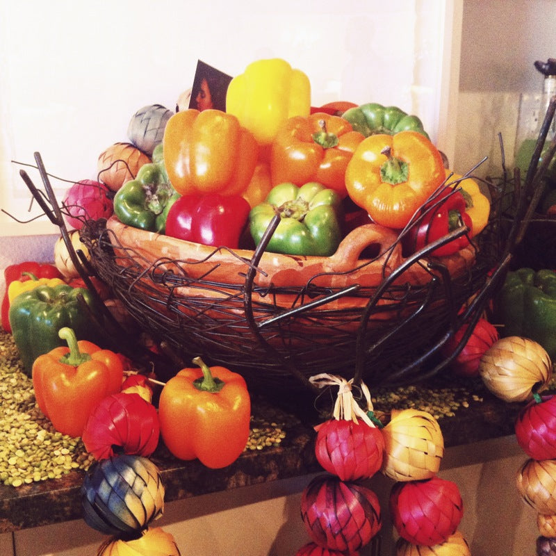 A large bowl full of colorful peppers with dried beans and paper onions around it