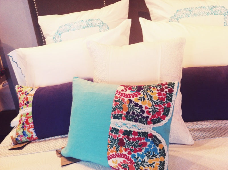 White and blue bedding accented with colorful Mexican floral fabrics