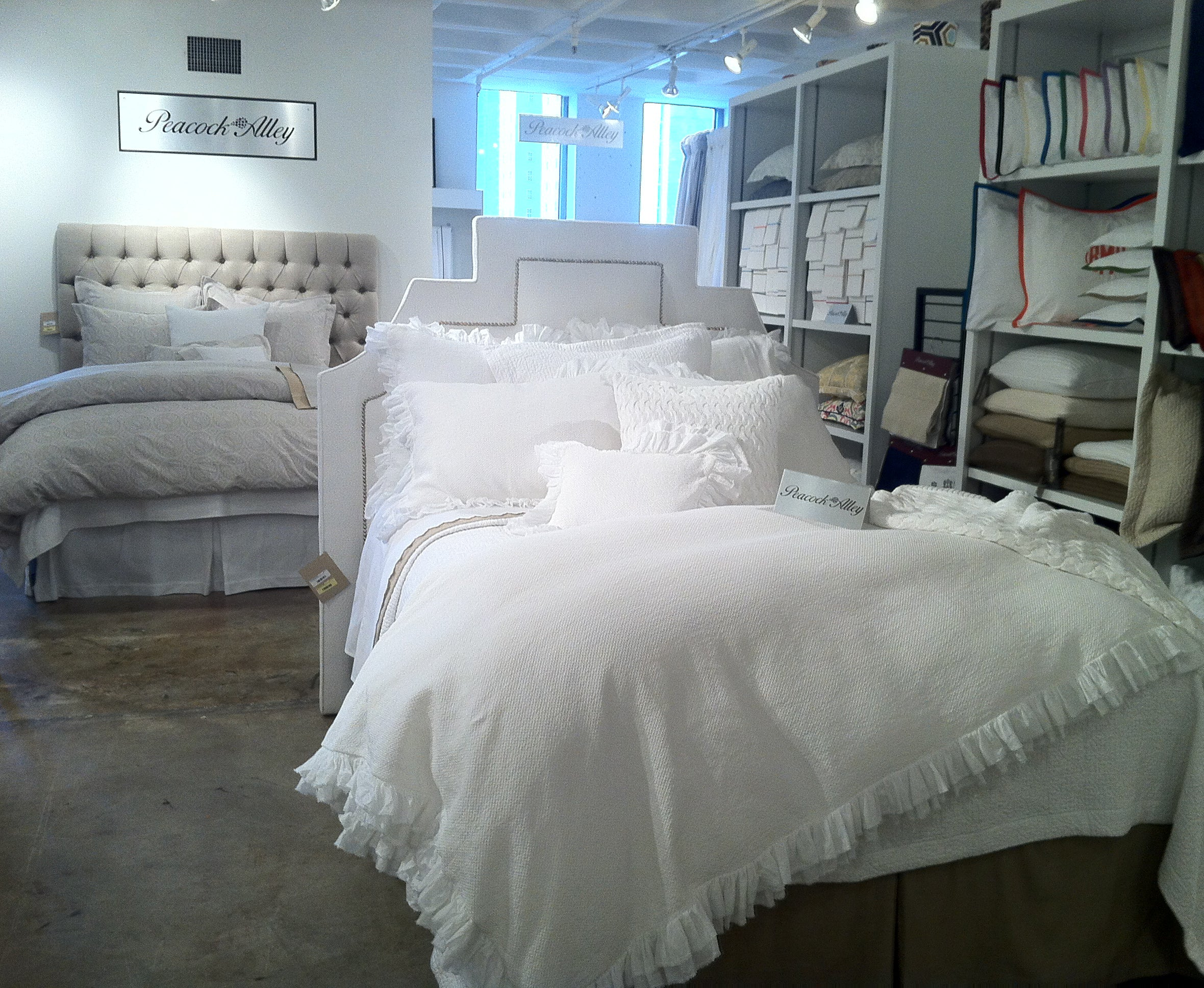 An all white ruffled bedding display with a neutral linen bed in the background