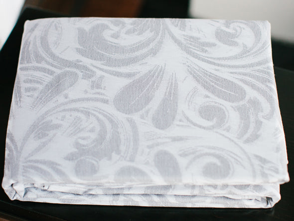 A folded duvet cover in a white and soft gray feminine pattern