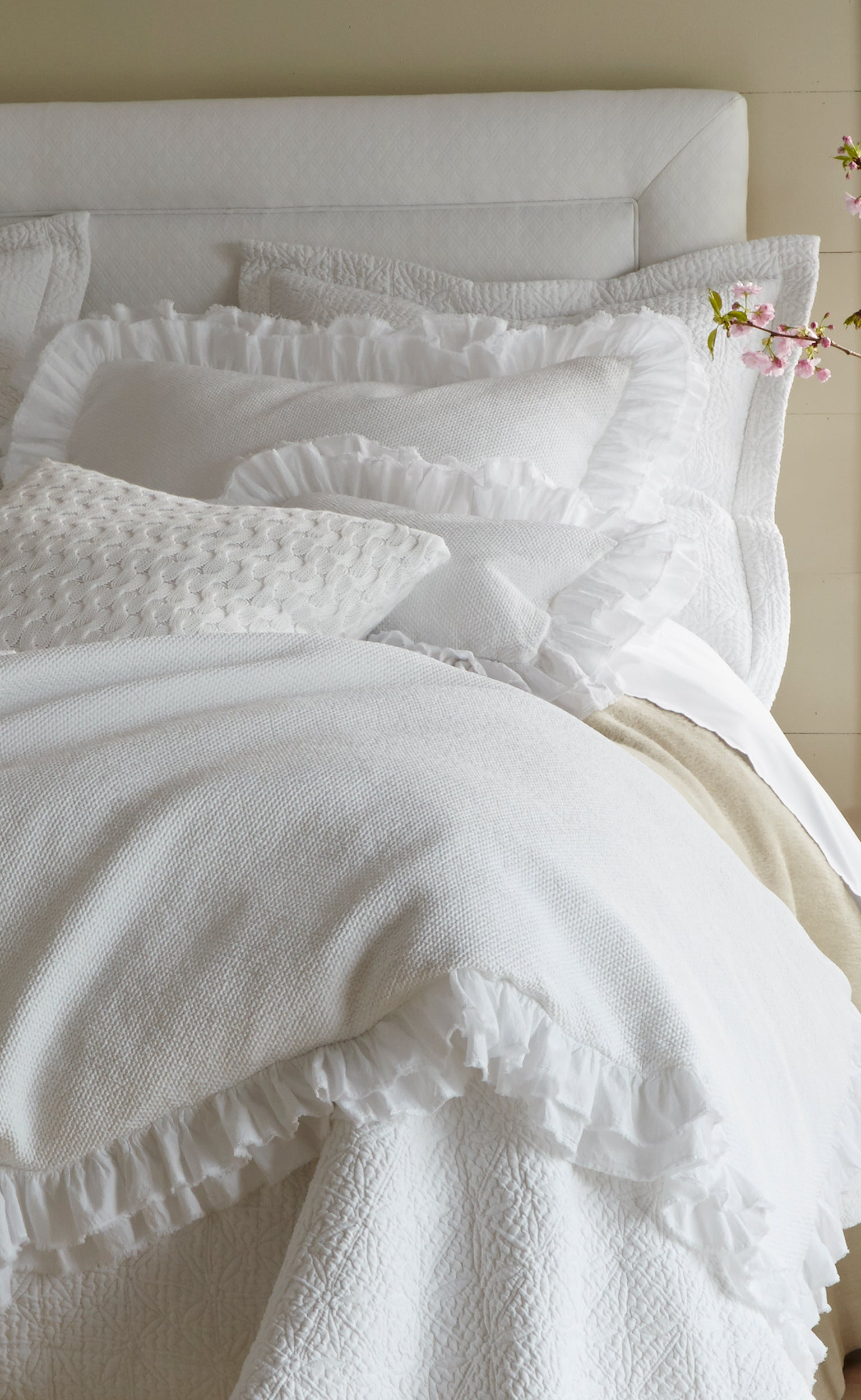 White layered bedding for chilly winter nights, with ruffles and matelassé accents