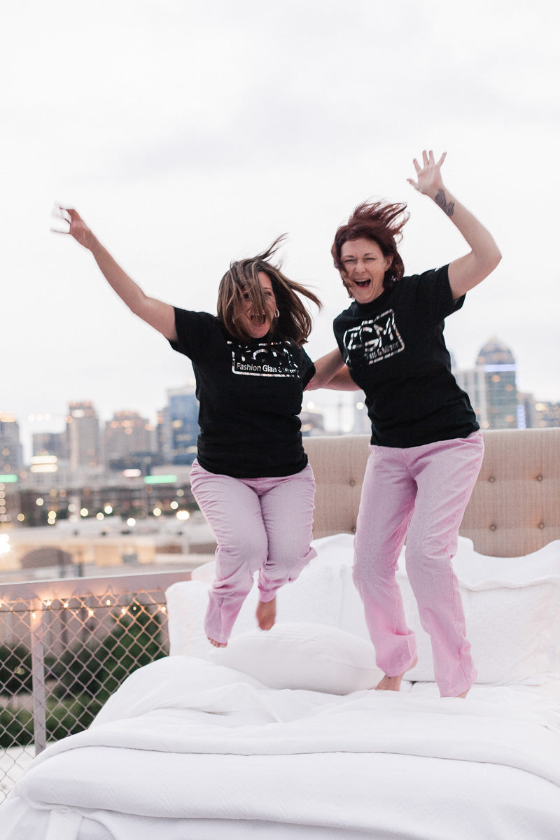 Two women jumping on a bed on a rooftop overlooking the Dallas skyline