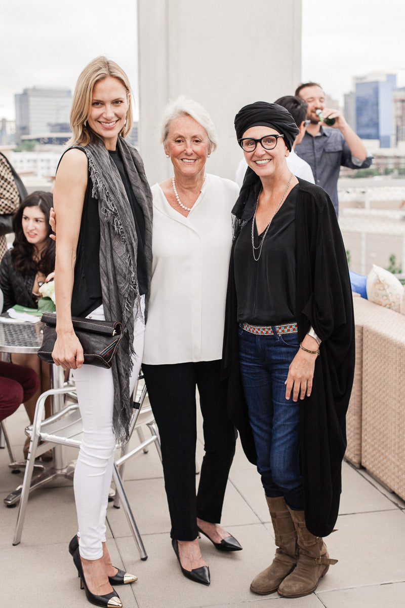 Mary Ella Gabler poses with guests on a rooftop overlooking the Dallas skyline at Peacock Alley's annual Sleep Under the Stars event