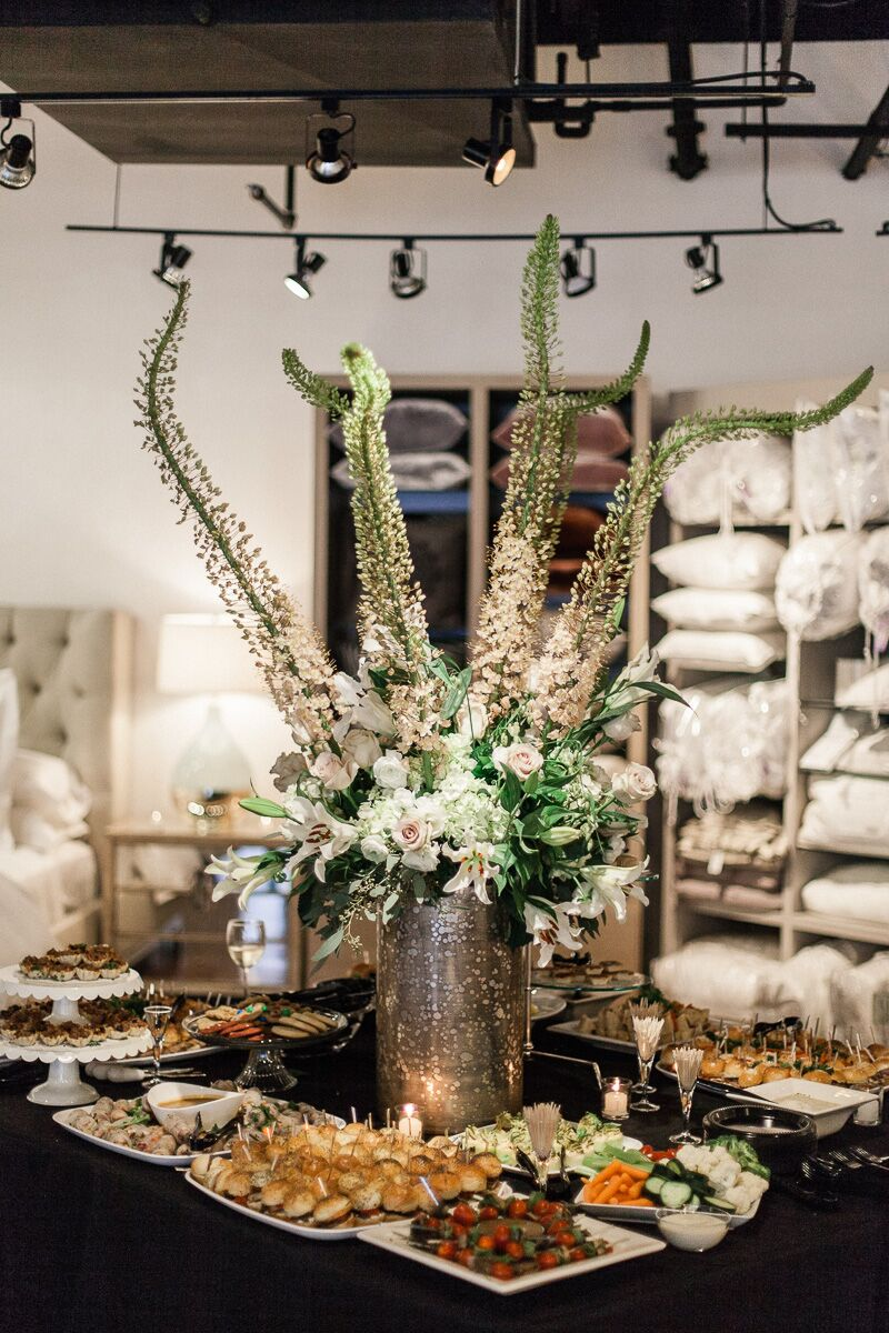 Finger foods and a towering flower arrangement on a table in front of a linens display