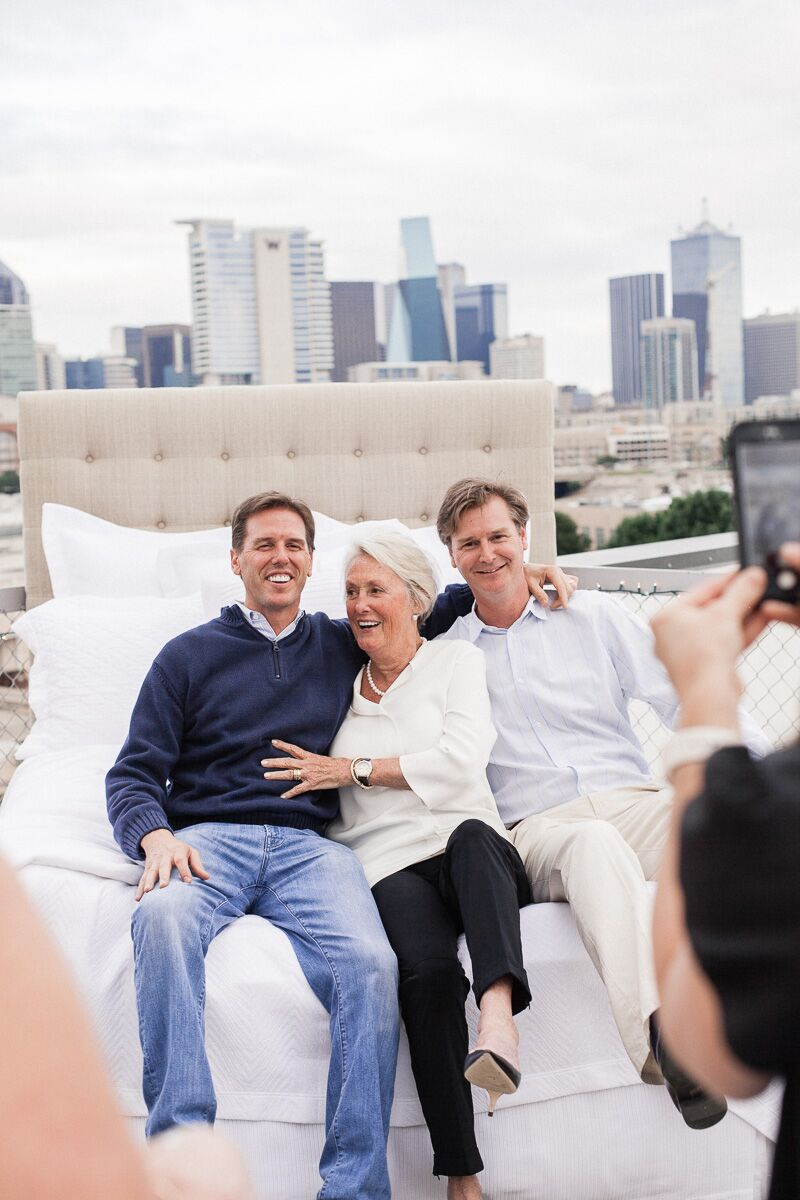 Josh Needleman, Mary Ella Gabler, and Jason Needleman pose on a rooftop bed, with the city of Dallas in the background