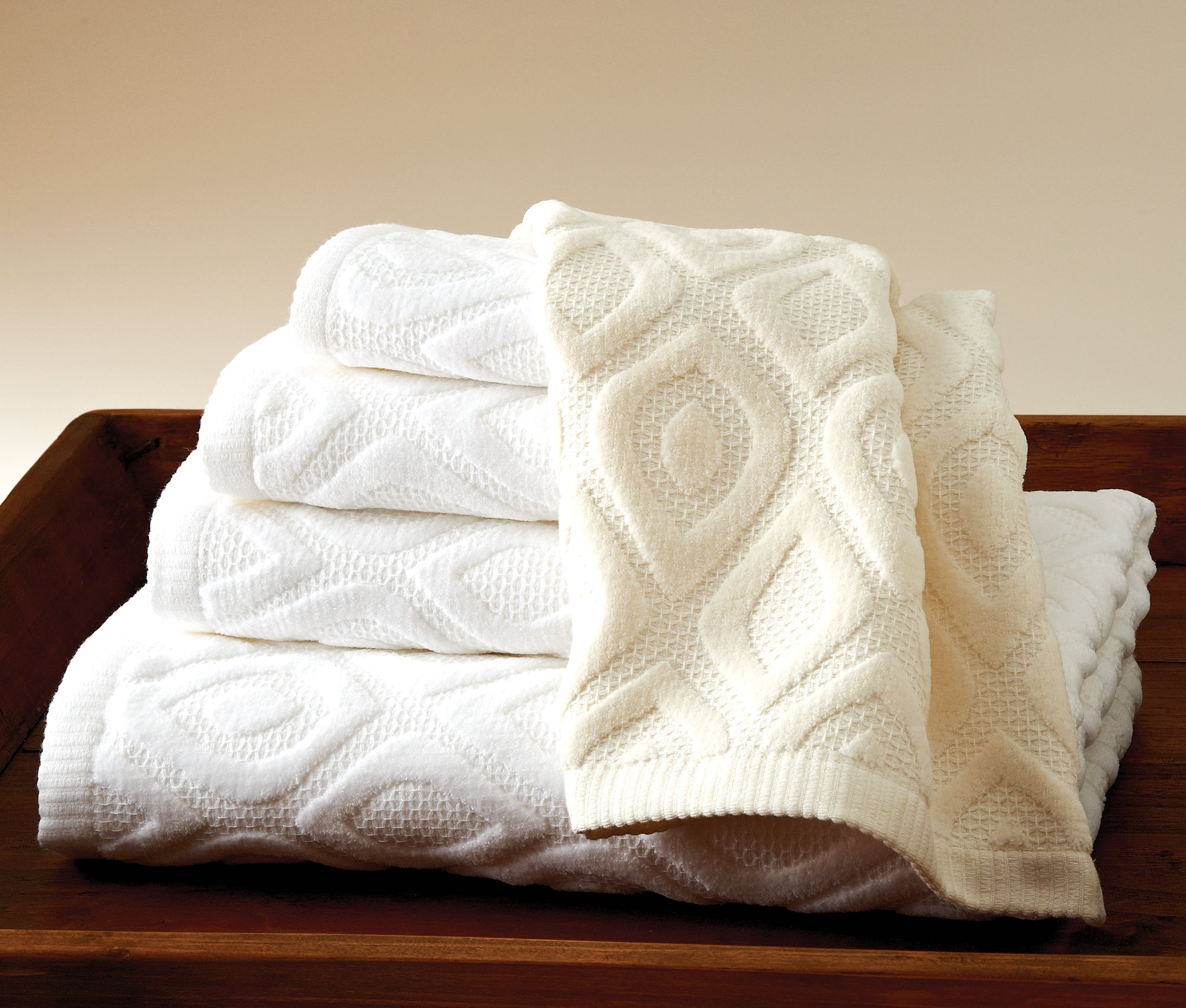 Stack of folded white towels with peacock feather texturing