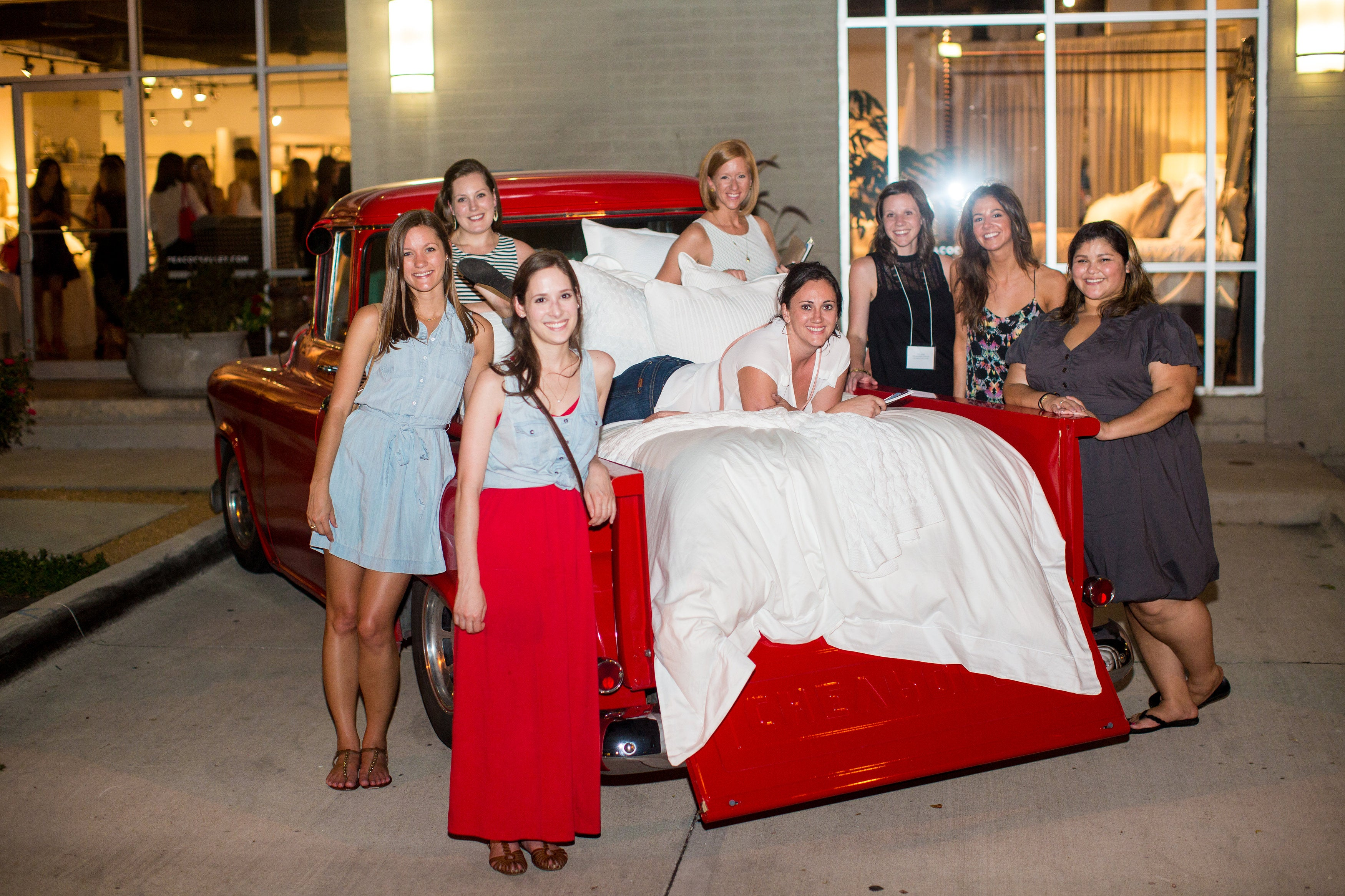 Eight ladies pose with a bed made in the bed of a classic, candy-apple-red Chevy pickup truck