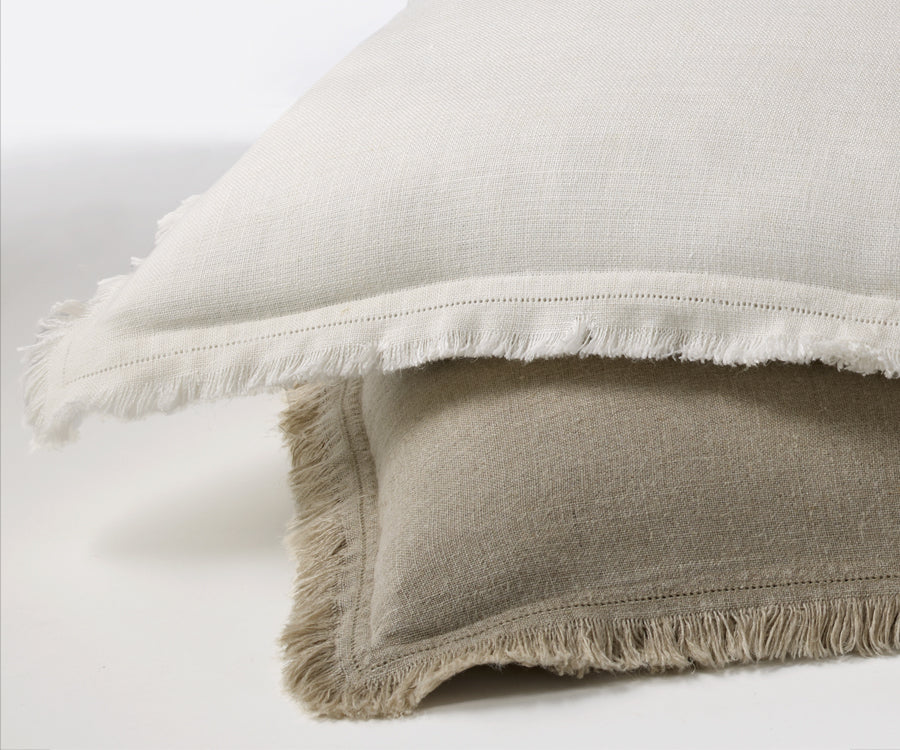 Distressed linen shams in white and tan with frayed edges