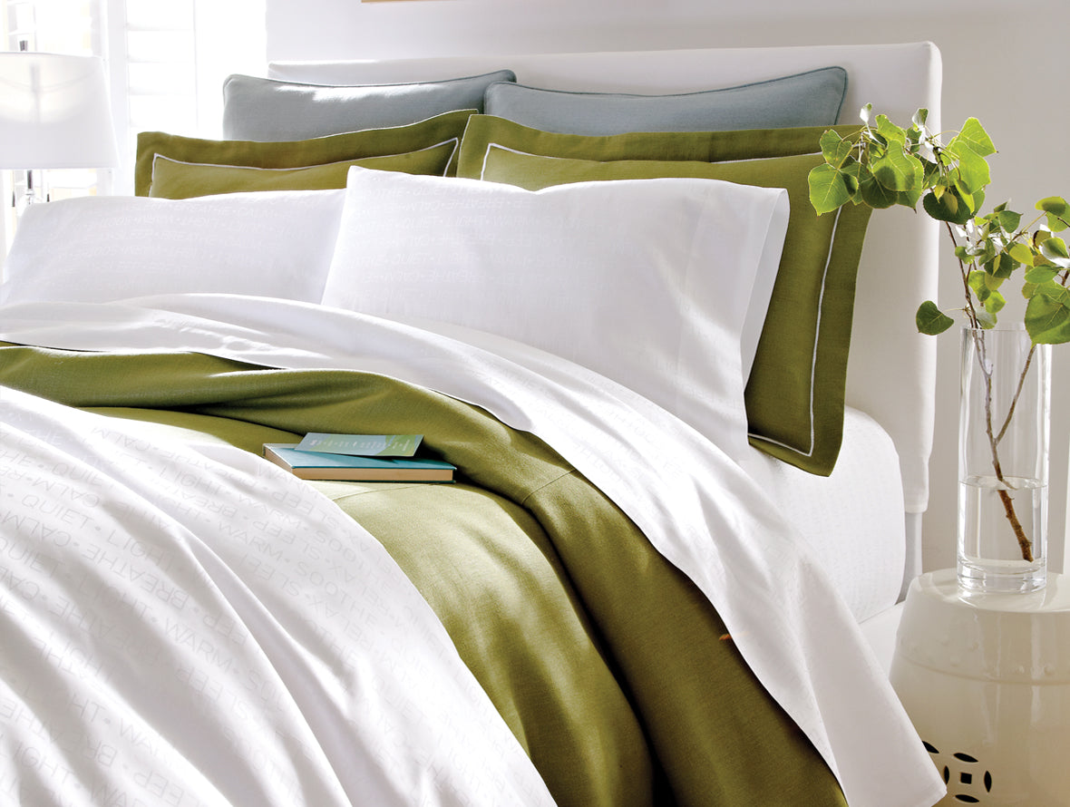 A modern bed in shades of white and green, featuring Intentions Linens with calming words subtly woven into the fabric