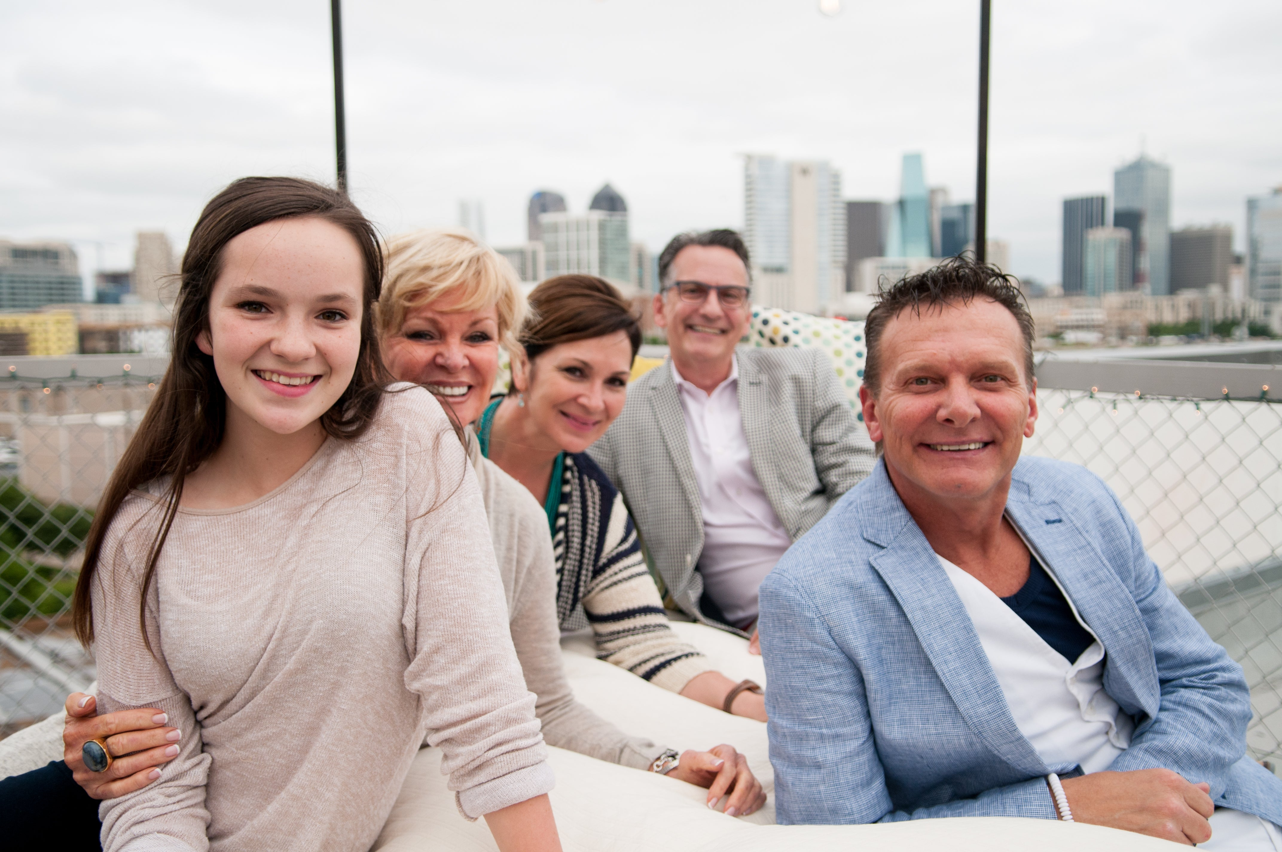 Guests pose on the rooftop in front of the Dallas skyline