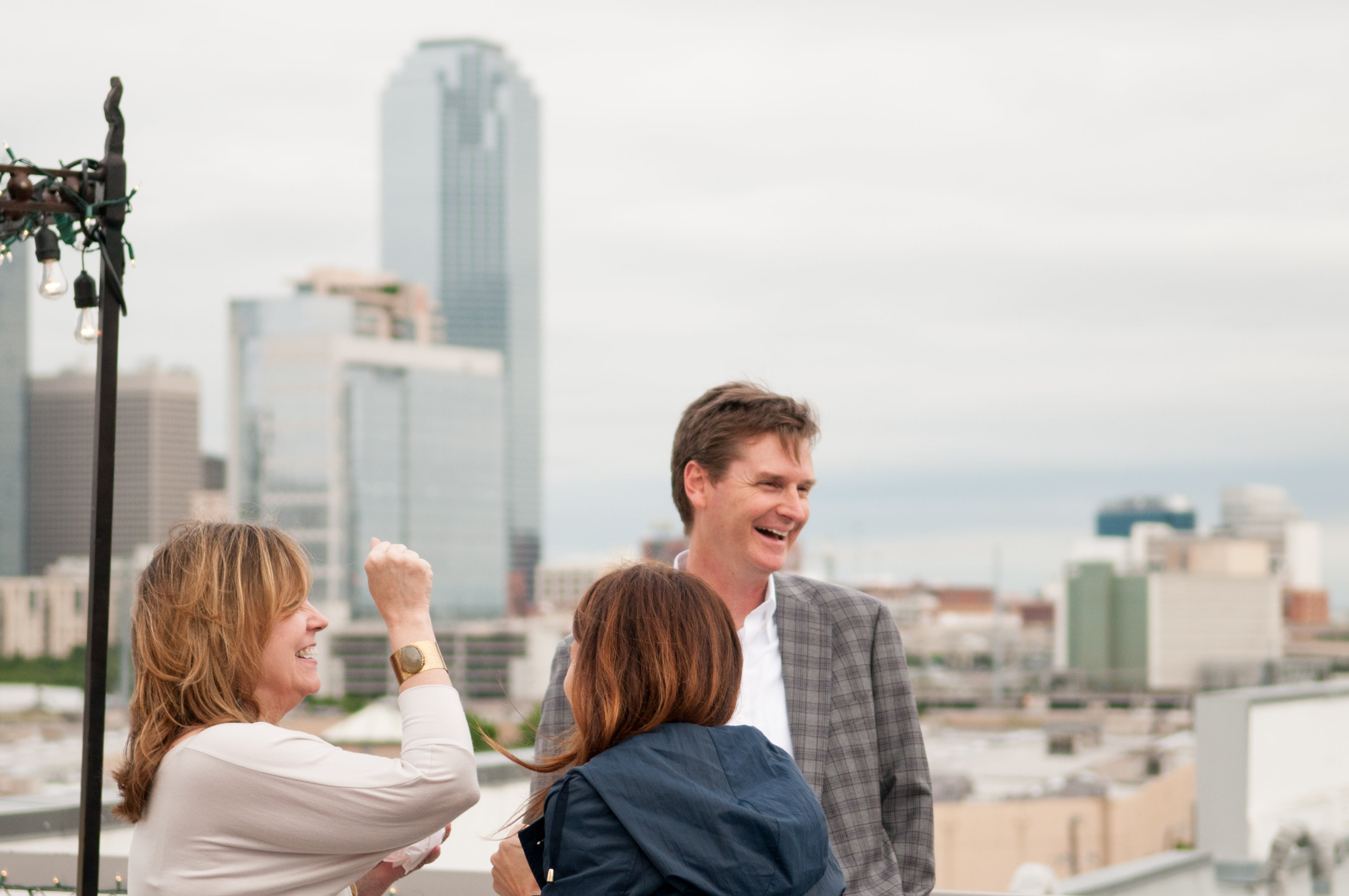 Jason Needleman laughs with guests on the rooftop overlooking the Dallas skyline