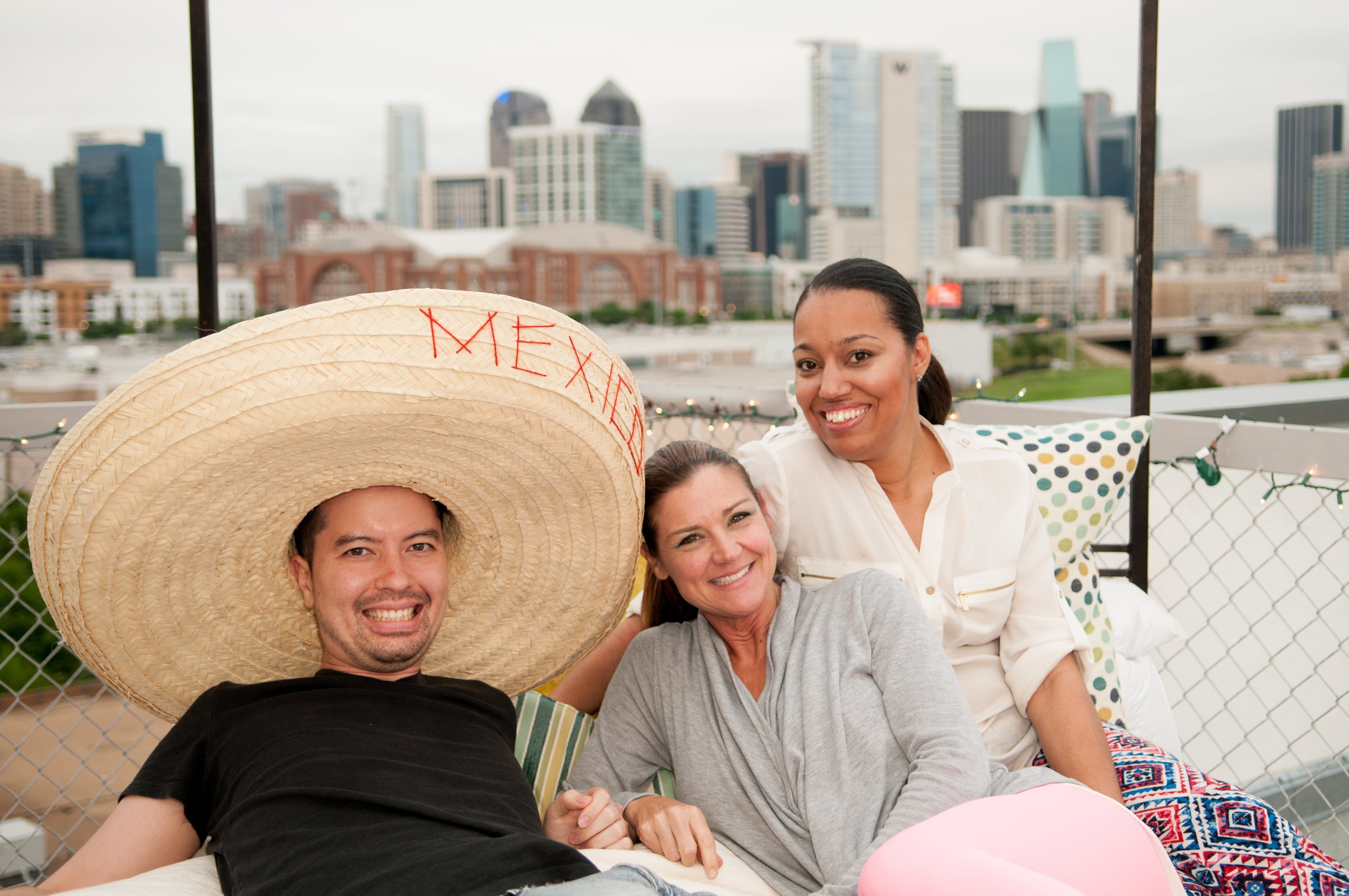 Guests lounge on the rooftop bed with a sombrero