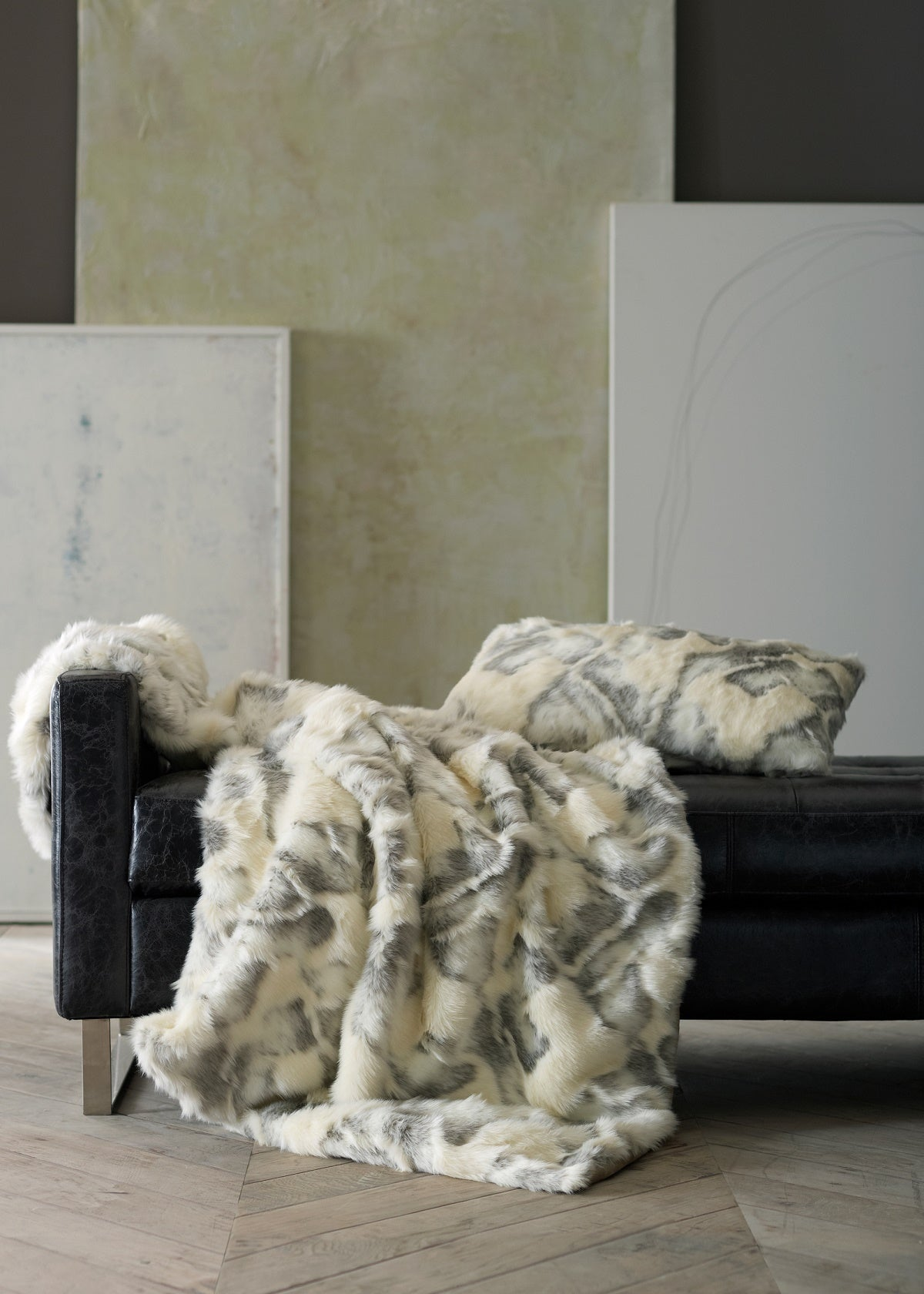 Faux fur in white and gray draped over black leather seating