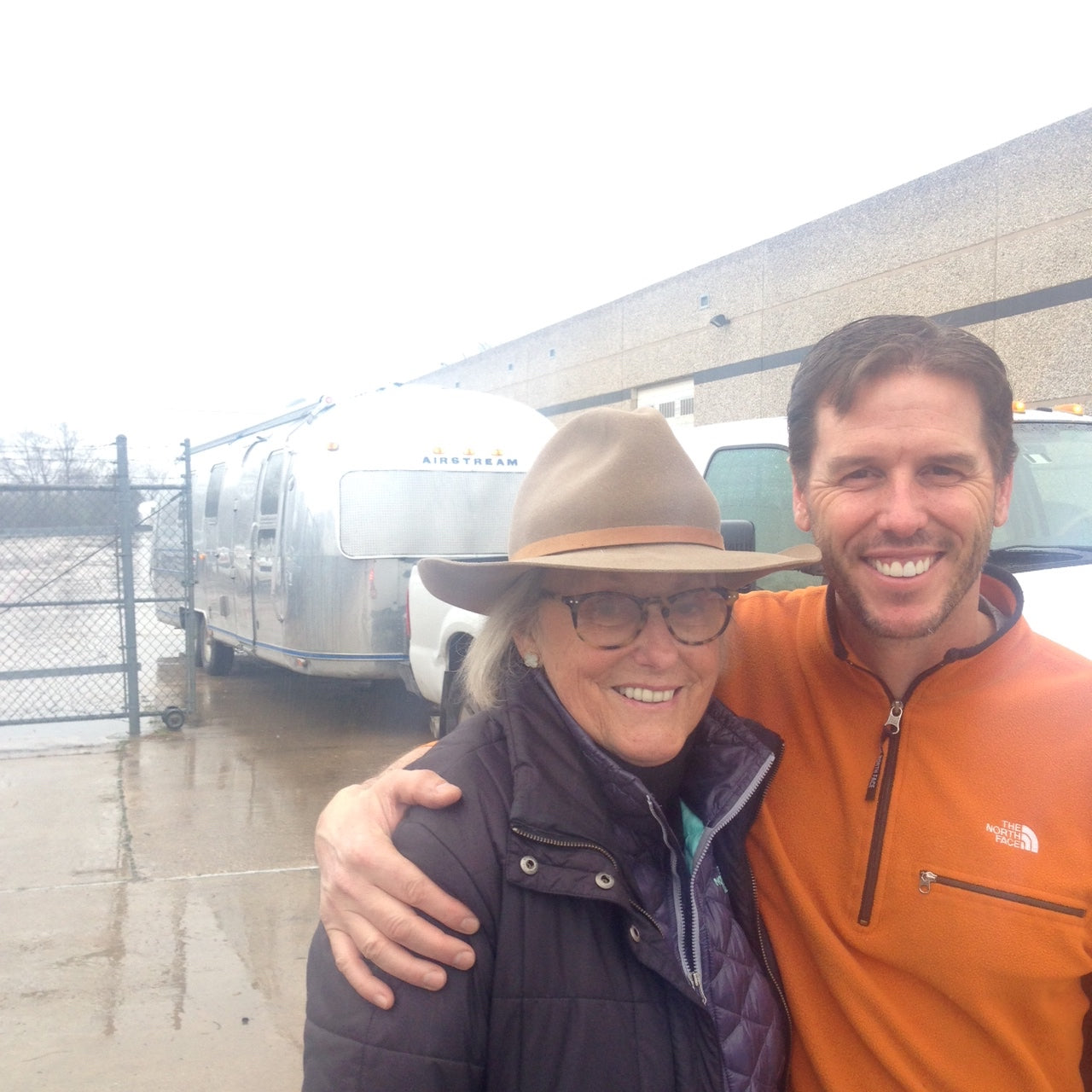 Mary Ella Gabler and Josh Needleman pose in front of the Steel Magnolia Airstream on a rainy day