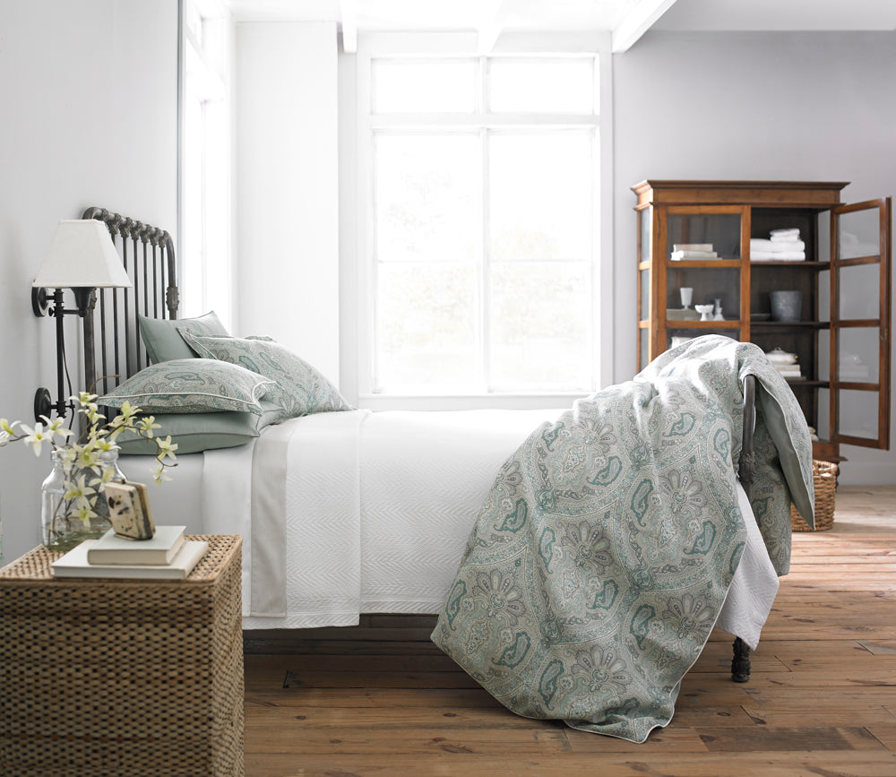 Classic bed styled in crisp white bedding with sage accents in a paisley pattern