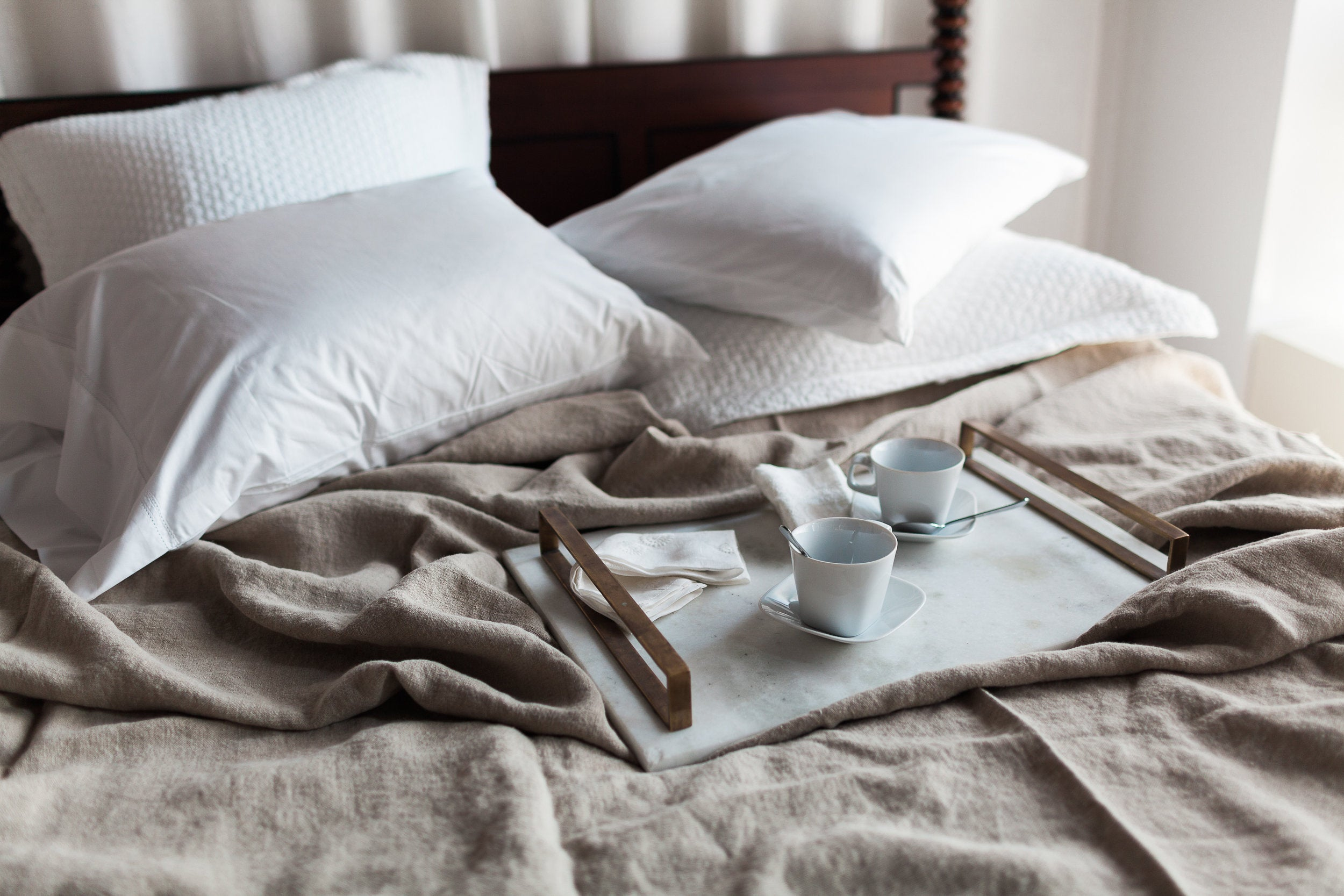 Messy bed layered for hot summer weather with tray and coffee mugs