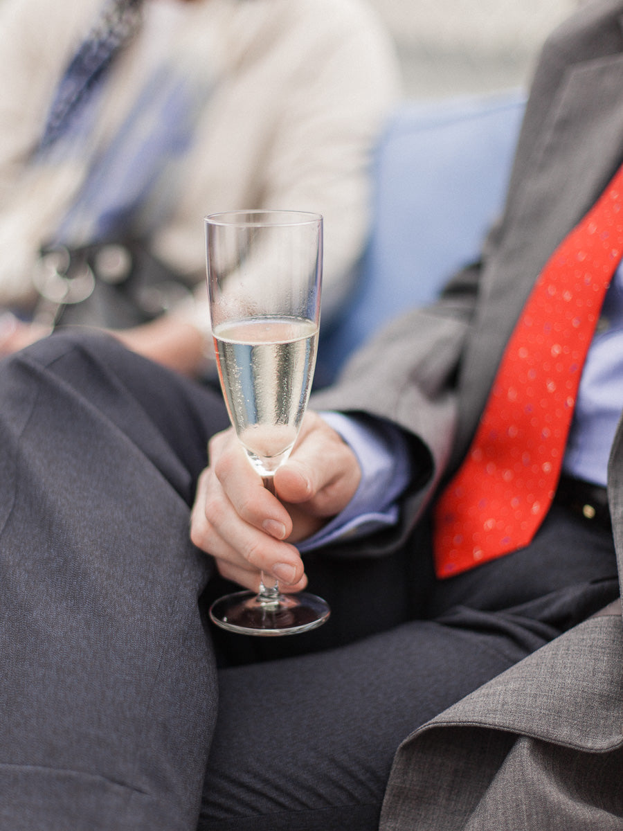 Man in a suit and tie holding a champagne glass