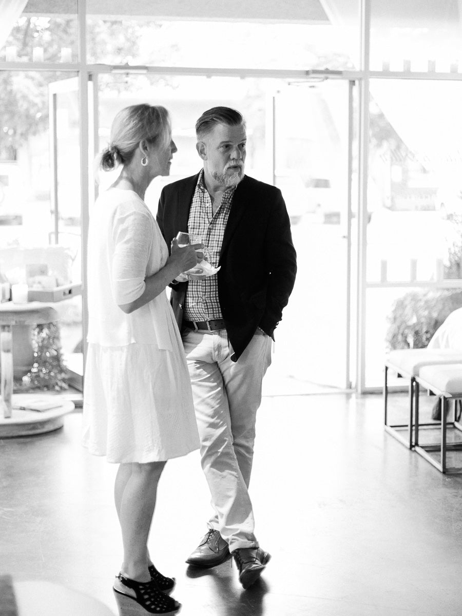Black and white candid portrait of a man and woman talking in front of open shop doors