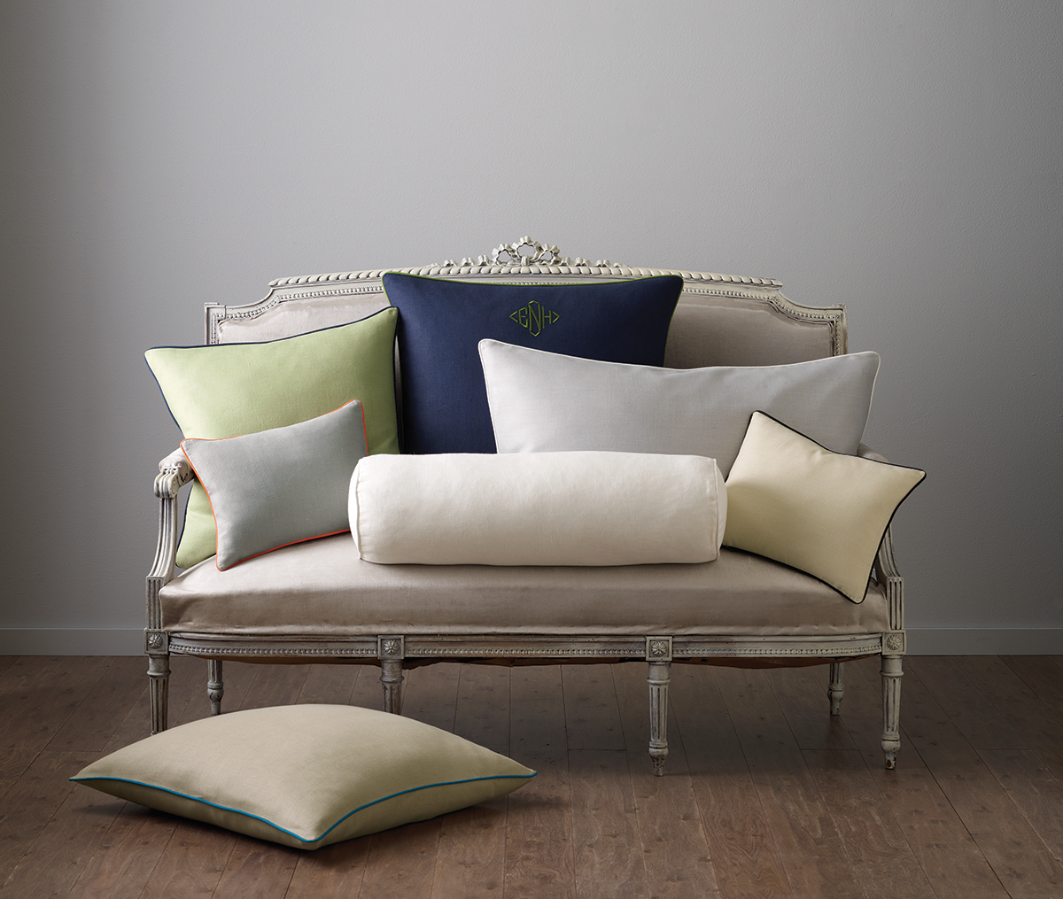 Neutral sofa piled with pillows in shades of blue, green, yellow, and neutrals