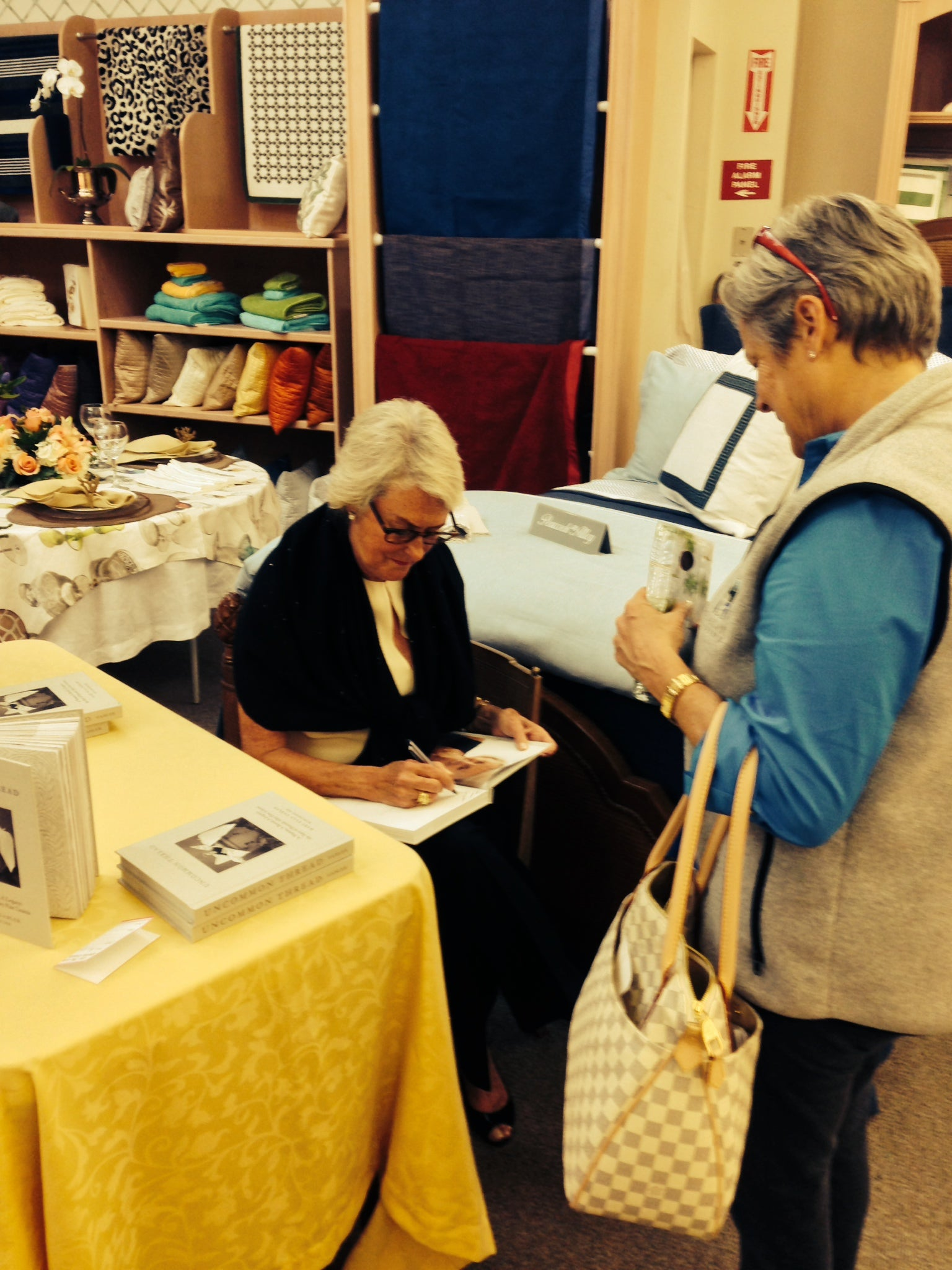 Mary Ella Gabler signs her book, Uncommon Thread, for a guest