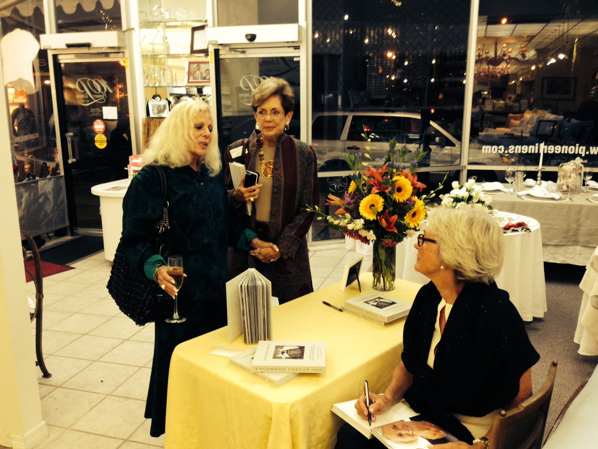 Mary Ella Gabler visiting with guests as she signs a copy of her book, Uncommon Thread