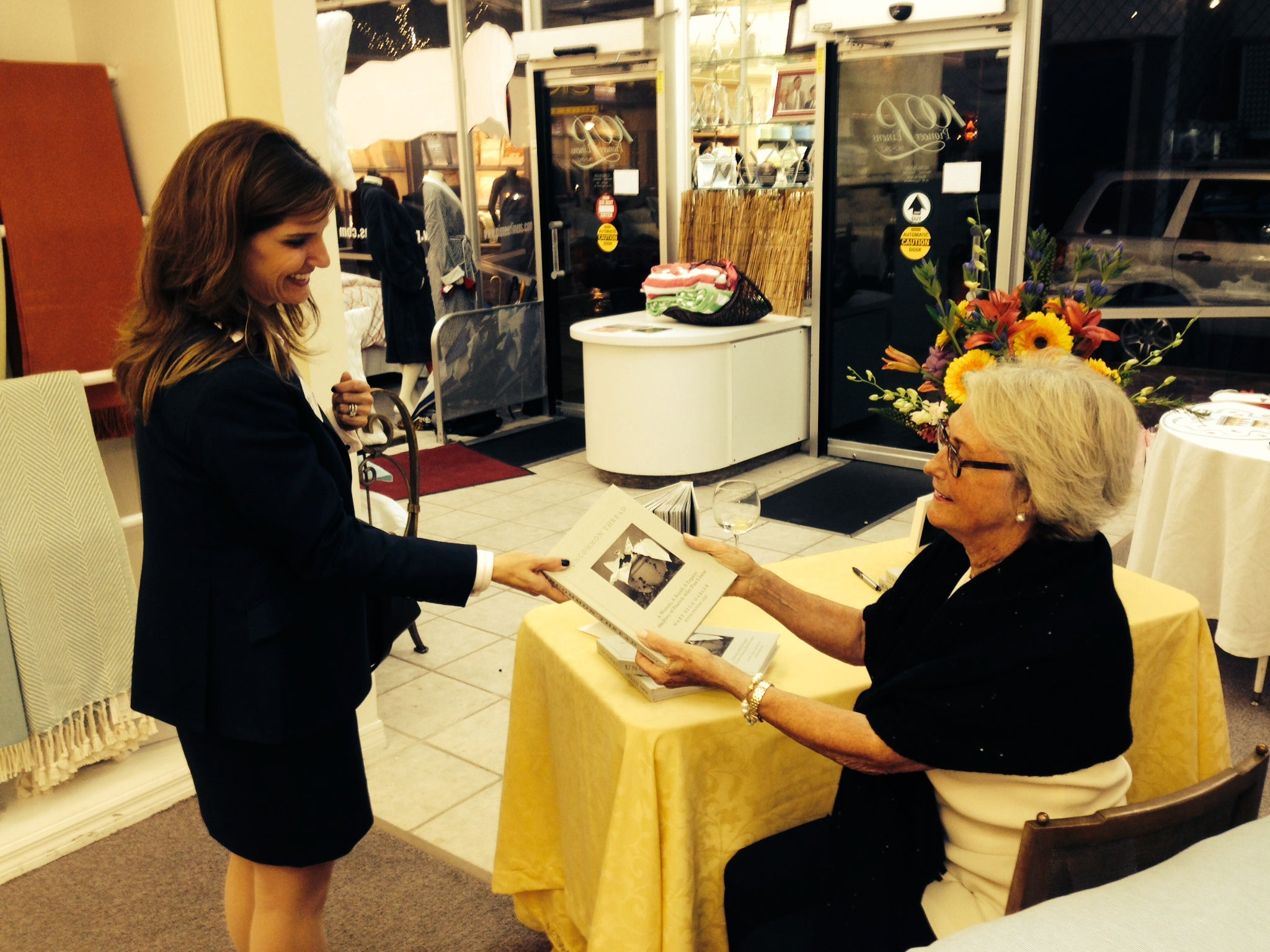 Mary Ella Gabler presents a signed copy of her book, Uncommon Thread, to a guest at a trunk show