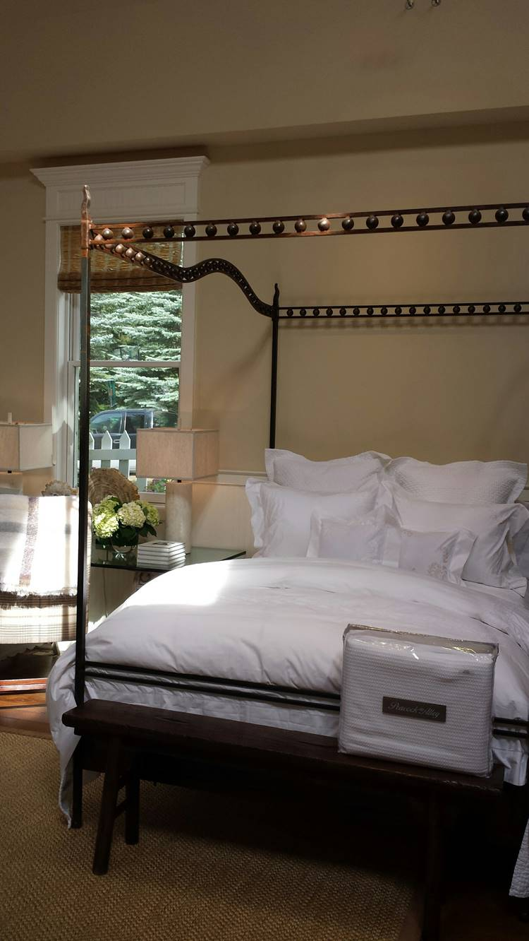 All white linens on a metal canopy bed