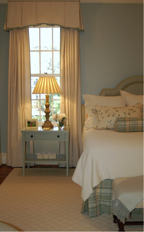 A modern country bedroom styled in green and linen