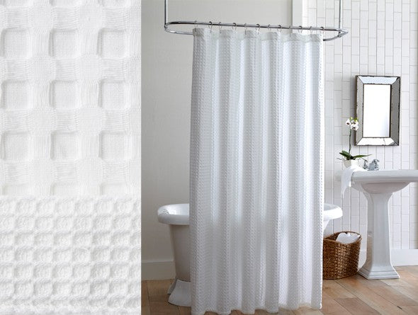 White waffle textured shower curtain in a mostly white bathroom